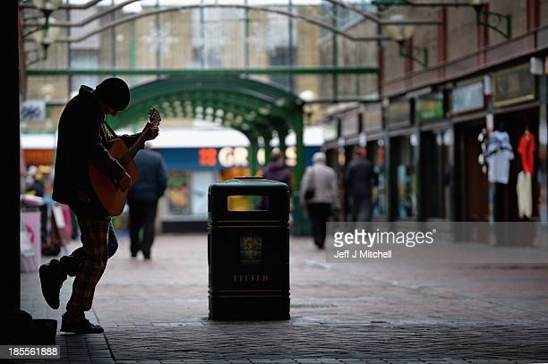 A busker plays in the town centre near Grangemouth oil refinery on October 22 2013 in Grangemouth Scotland Ineos who operate the oil refinery are set...