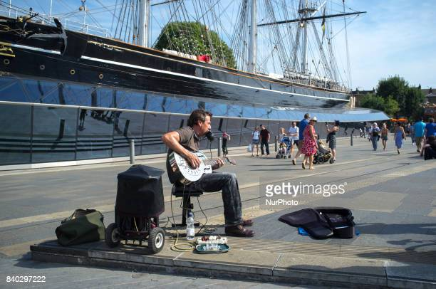 A busker plays near Cutty Sark at Greenwich London on August 28 2017 The August Bank Holiday have seen sunny weather and hot temperature People...