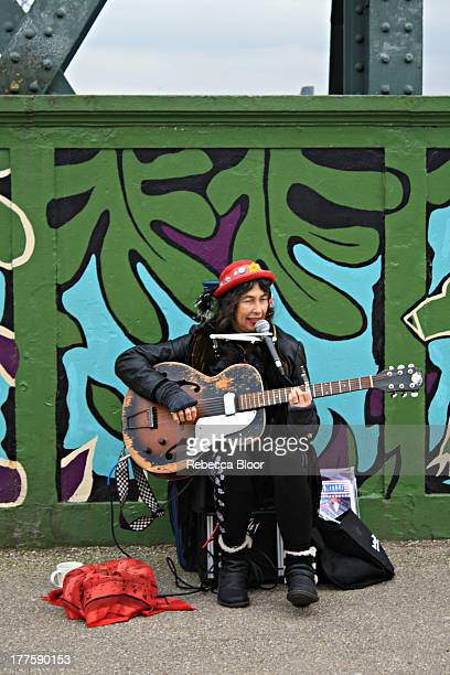 Busker - Primrose Hill, North London, 2012. Performing on bridge with graffiti in background