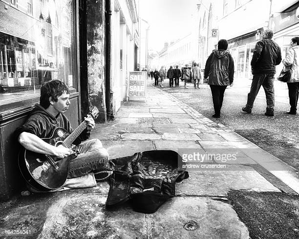 Busker , singing and playing guitar on the streets of the historic fishing town of Whitby, England....People took little or no notice of him and just...