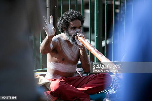 Busker sitting and blowing didgeridoo