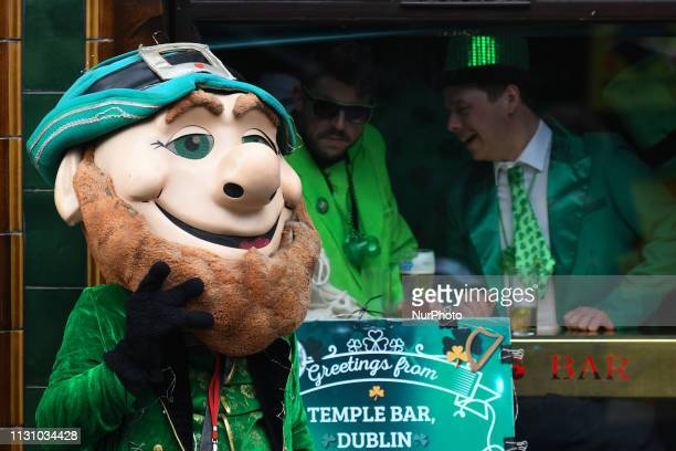 A busker with a leprechaun costume with tourists enjoy in the background in Temple Bar on the eve of St Patrick's Day celebrations On Saturday March...