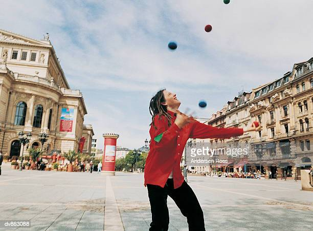 Busker With Dreadlocks Juggling in a Town Square
