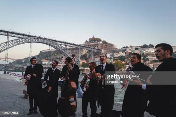 Buskers band performing along Douro River at sunrise with Dom Luis I bridge, Porto, Portugal