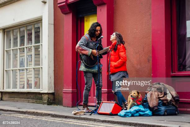 busking couple with dog - busker stock pictures, royalty-free photos & images