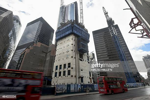 Busses drive past the construction site of the partially built 'The Pinnalce' skyscraper in Bishopsgate London on February 21 2015 French real estate...