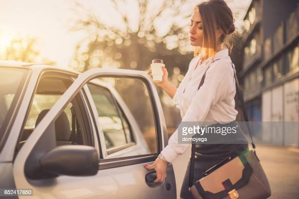 Bussines woman getting into car