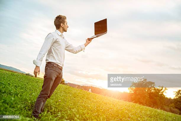 Bussinesman holding computer in the air , outside in nature