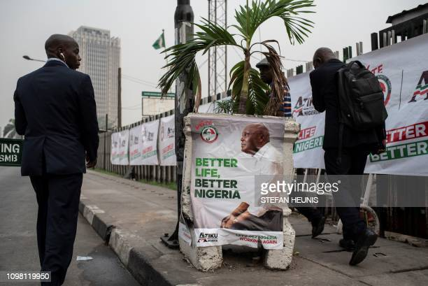 TOPSHOT Bussiness men walk past a campaign poster for presidential candidate Atiku Abubakar from the Peoples Democratic Party on February 12 2019 in...