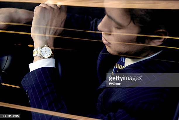 Bussinessman Driving Looking At Watch