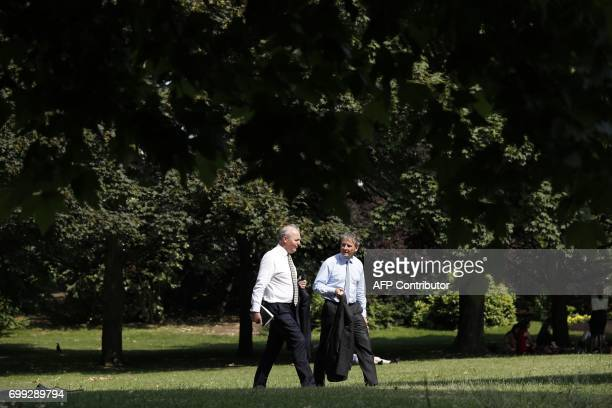 Bussinessmen walk in the hot weather in St James's Park in central London on June 21 2017 Europe sizzled under a continentwide heatwave on June 21...