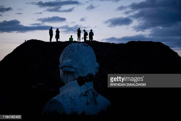 A bust of former US President George Washington can be seen as people get an overview from a mountain of mulch while they tour the decaying remains...