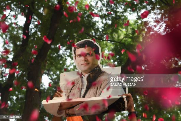 A bust placard of All India Congress Committee President Rahul Gandhi is seen through a shower of rose petals as Congress party supporters celebrate...