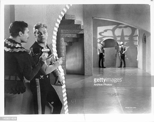 Buster Crabbe listening to man before turning corner in a scene from the film 'Flash Gordon' 1936