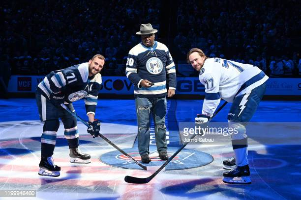 Buster Douglas drops the honorary puck for Nick Foligno of the Columbus Blue Jackets and Victor Hedman of the Tampa Bay Lightning prior to a game on...