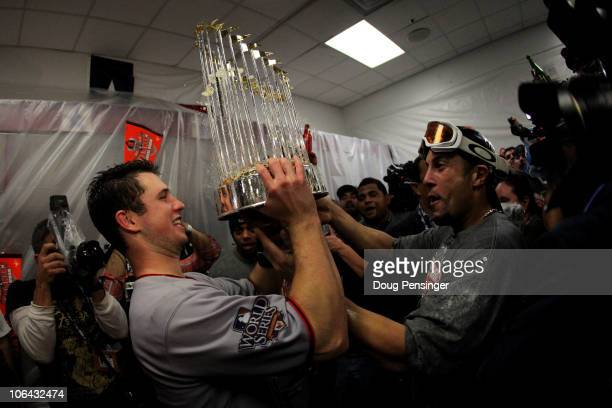 Buster Posey and Andres Torres of the San Francisco Giants celebrates with the trophy in the locker room after the Giants won 3-1 against the Texas...