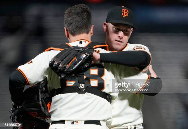 Buster Posey and Anthony DeSclafani of the San Francisco Giants celebrate after DeSclafani pitched a complete game to defeat the Colorado Rockies...