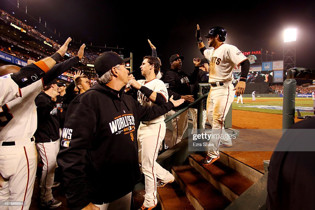 Buster Posey #28 and Gregor Blanco #7 of the San Francisco Giants celebrate after scoring in the sixth inning against the Kansas City Royals during Game Four of the 2014 World Series at AT&T Park on October 25, 2014 in San Francisco, California.