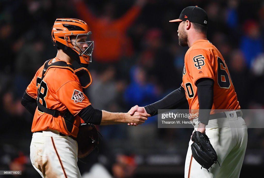 Buster Posey #28 and Hunter Strickland #60 of the San Francisco Giants celebrates defeating the Philadelphia Phillies 4-0 at AT&T Park on June 1, 2018 in San Francisco, California.