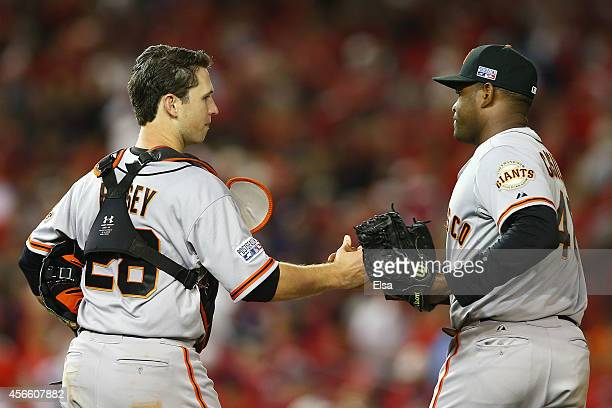 Buster Posey and Santiago Casilla of the San Francisco Giants celebrate their 3 to 2 win over the Washington Nationals during Game One of the...