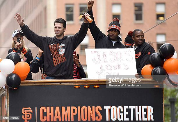 Buster Posey and Santiago Casilla of the San Francisco Giants waves to the crowd along the parade route during the San Francisco Giants World Series...