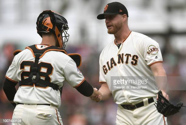 Buster Posey and Will Smith of the San Francisco Giants celebrate defeating the Milwaukee Brewers 85 at ATT Park on July 29 2018 in San Francisco...