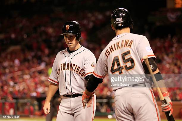 Buster Posey celebrates with Travis Ishikawa of the San Francisco Giants after scoring on a sacrafice fly by Brandon Belt in the third inning against...