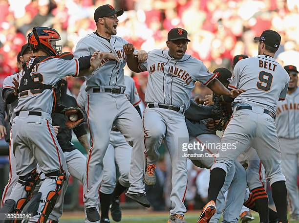 Buster Posey, George Kontos, Santiago Casilla and Brandon Belt of the San Francisco Giants celebrate a win against the Cincinnati Reds in Game Five...