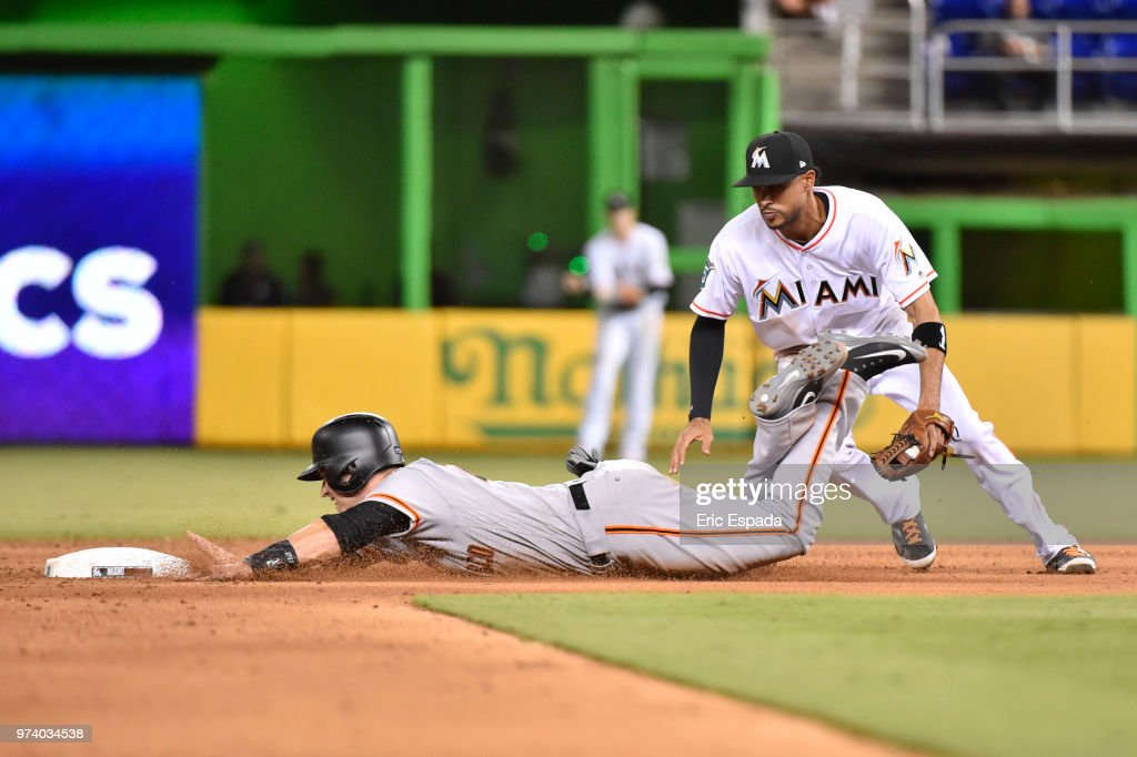 Buster Posey #28 of the San Francisco Giants avoids the tag of Yadiel Rivera #2 of the Miami Marlins as he steals second base in the ninth inning of the game at Marlins Park on June 13, 2018 in Miami, Florida.
