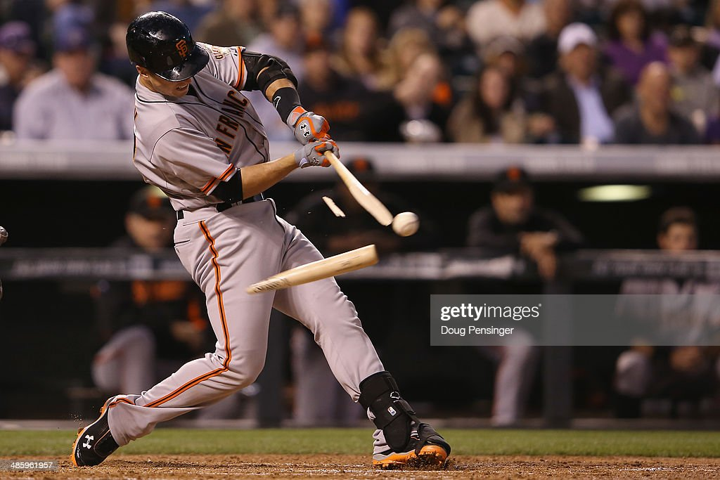 Buster Posey #28 of the San Francisco Giants breaks his bat as he hits into a double play and collects an RBI against the Colorado Rockies in the third inning at Coors Field on April 21, 2014 in Denver, Colorado.