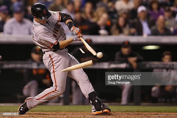 Buster Posey of the San Francisco Giants breaks his bat as he hits into a double play and collects an RBI against the Colorado Rockies in the third...