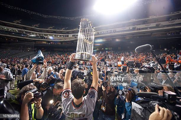 Buster Posey of the San Francisco Giants celebrates by holding up the World Series Trophy after defeating the Texas Rangers in Game Five of the 2010...
