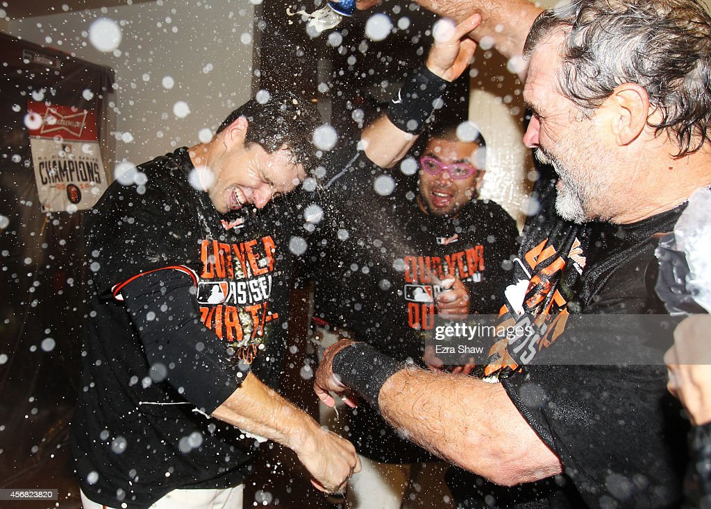 Buster Posey #28 (L) of the San Francisco Giants celebrates in the locker room after their 3 to 2 win over the Washington Nationals in Game Four of the National League Division Series at AT&T Park on October 7, 2014 in San Francisco, California.