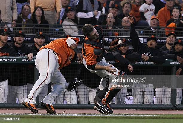 Buster Posey of the San Francisco Giants collides with Pablo Sandoval trying to field a foul ball during the first inning of the National League...