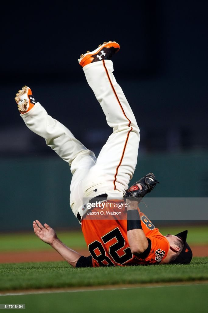 Buster Posey #28 of the San Francisco Giants falls backwards after catching a fly ball hit off the bat of Jake Lamb (not pictured) of the Arizona Diamondbacks during the first inning at AT&T Park on September 15, 2017 in San Francisco, California.