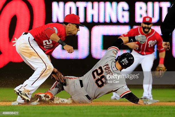 Buster Posey of the San Francisco Giants gets tagged out by Ian Desmond of the Washington Nationals after attempting to steal second base in the...