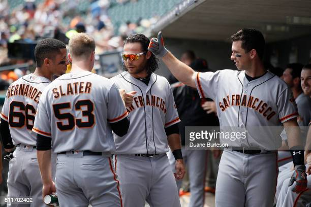 Buster Posey of the San Francisco Giants gives a thumbs up to teammates Gorkys Hernandez of the San Francisco Giants Austin Slater of the San...