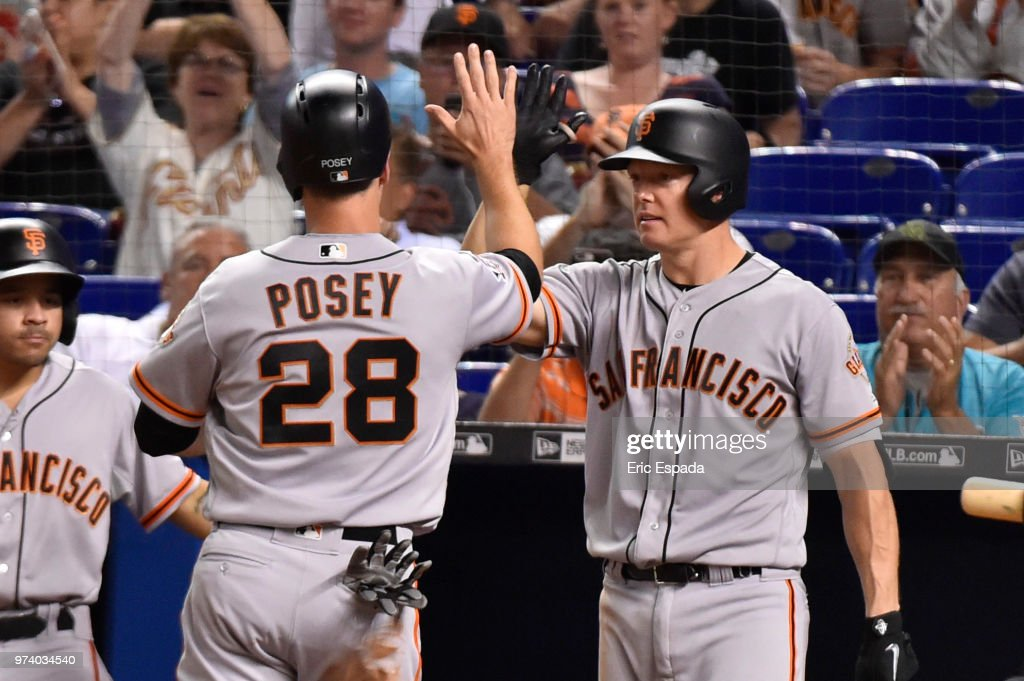 Buster Posey #28 of the San Francisco Giants high fives Nick Hundley #5 after scoring in the seventh inning against the Miami Marlins at Marlins Park on June 13, 2018 in Miami, Florida.