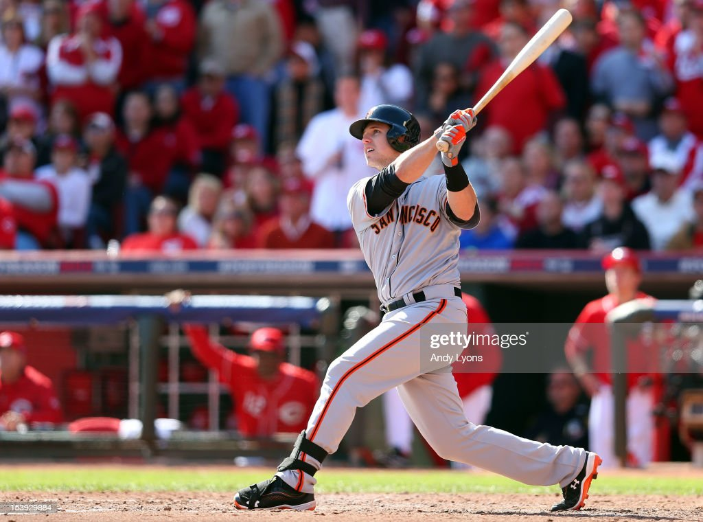 Buster Posey #28 of the San Francisco Giants hits a grand slam in the fifth inning against the Cincinnati Reds in Game Five of the National League Division Series at Great American Ball Park on October 11, 2012 in Cincinnati, Ohio.
