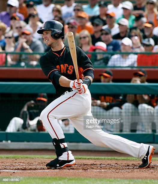 Buster Posey of the San Francisco Giants hits a ground ball against the Milwaukee Brewers during the first inning of a Cactus League game at...