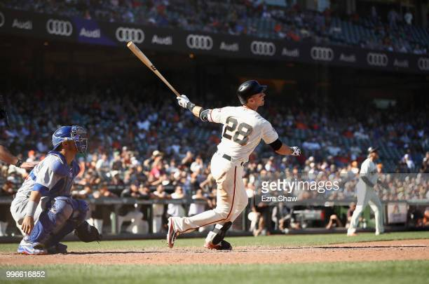 Buster Posey of the San Francisco Giants hits the game winning hit in the bottom of the 13th inning to beat the Chicago Cubs at AT&T Park on July 11,...