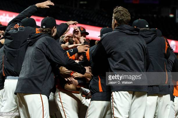 Buster Posey of the San Francisco Giants is congratulated by teammates after hitting a walk off home run against the Cincinnati Reds during the...