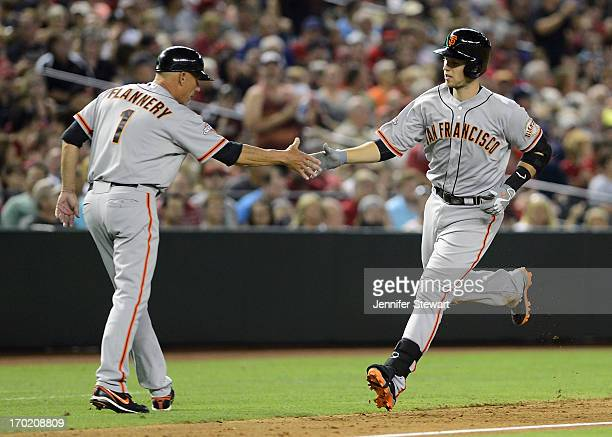 Buster Posey of the San Francisco Giants is congratulated by third base coach Tim Flannery after hitting a two un home run against the Arizona...