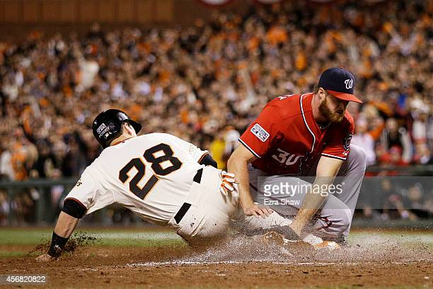 Buster Posey of the San Francisco Giants is out at home plate by Aaron Barrett of the Washington Nationals in the seventh inning during Game Four of...