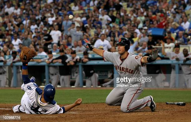 Buster Posey of the San Francisco Giants looks for the call after sliding safely into home with a run as catcher Russell Martin of the Los Angeles...