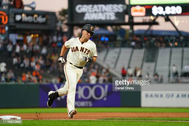 Buster Posey of the San Francisco Giants rounds the bases after hitting a two run home run during the first inning against the Colorado Rockies at...