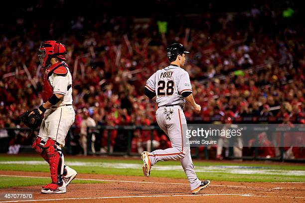 Buster Posey of the San Francisco Giants runs home to score on a sacrafice fly in the third inning against the St. Louis Cardinals during Game One of...
