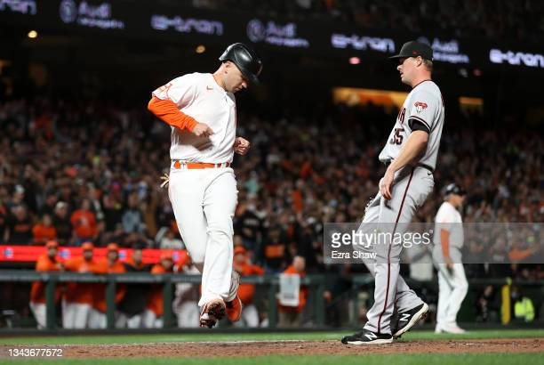 Buster Posey of the San Francisco Giants runs home to score on a wild pitch by Joe Mantiply of the Arizona Diamondbacks in the sixth inning at Oracle...