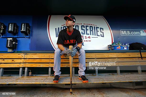 Buster Posey of the San Francisco Giants sits in the dugout during batting practice prior to Game Two of the 2014 World Series against the Kansas...