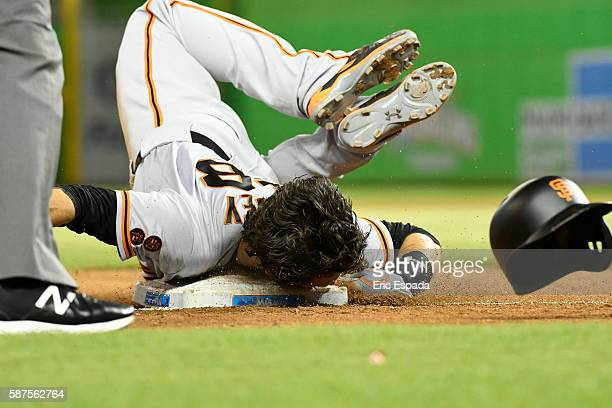 Buster Posey of the San Francisco Giants slides awkwardly into 3rd base after a single by Brandon Crawford in the 11th inning against the Miami...